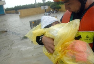A man carries a baby as a family is rescued from flooding brought by Typhoon Morakot in Chiatung, Pingtung county, in southern Taiwan, on August 9, 2009. (PATRICK LIN/AFP/Getty Images)