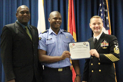 Acting Commander of the Coast Guard, Brenton Cain, left, AB Damian Franklyn, centre, flanked by a member of the United States Naval Ordnance Disposal School.