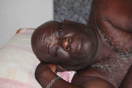 Glaston Hunte, A Friend Of The Deceased Man, Has A Problem With His Legs. He Is Photographed Lying On The Bed He Was On When The Robber Entered The Room On Friday.