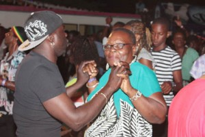 An elderly woman dances with a younger man during Soca Fest on Saturday.