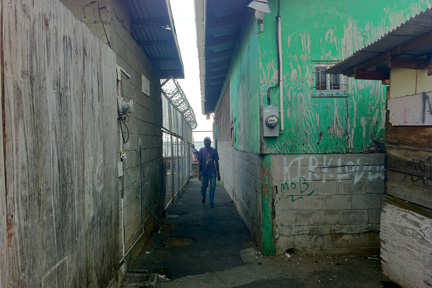 A man walks along the alleyway leading to the temporary meat market in Kingstown on Friday, April 5, 2013. Butcher say the area is unsanitary and unsafe.